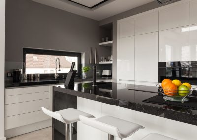 Cuisine moderne, comptoir en granit noir et îlot en granit noir.
