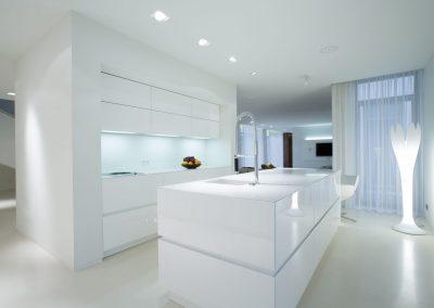Cuisine ultra moderne blance. Comptoir et îlot blanc en quartz. design épuré.